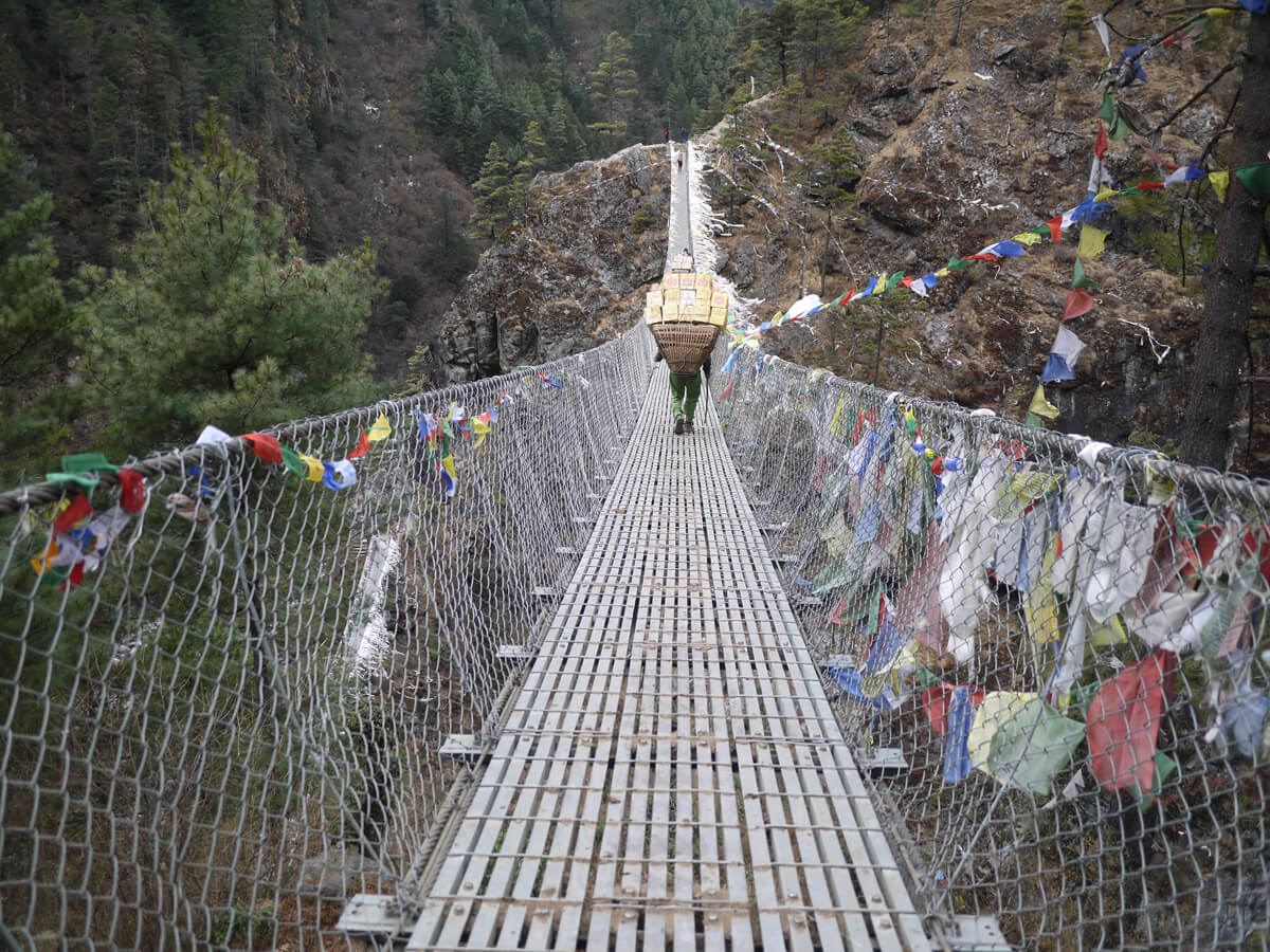 Crossing steel bridge on the route of Everest Base Camp Trekking
